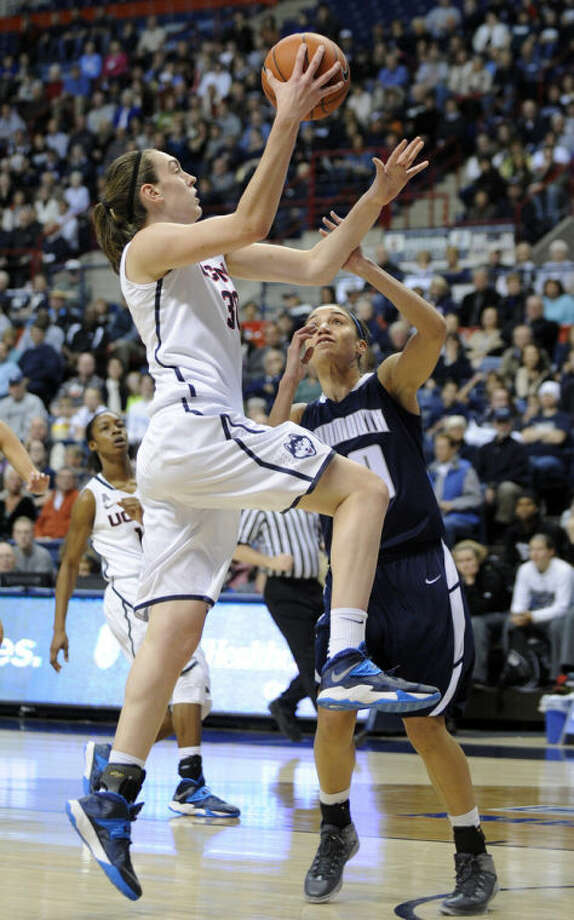Connecticut's Breanna Stewart (30) drives past Monmouth's Chevannah Paalvast during the first half of an NCAA college basketball game, in Storrs, Conn., on Saturday, Nov. 23, 2013. (AP Photo/Fred Beckham)