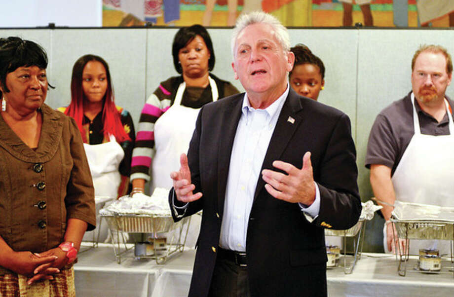 Hour photo / Erik Trautmann The new mayor of Norwalk, Harry Rilling, addresses volunteers and guests as the Rev. Nellie Mann hosts her annual pre-Thanksgiving feast for the needy at Calvary Baptist Church Saturday. / (C)2013, The Hour Newspapers, all rights reserved