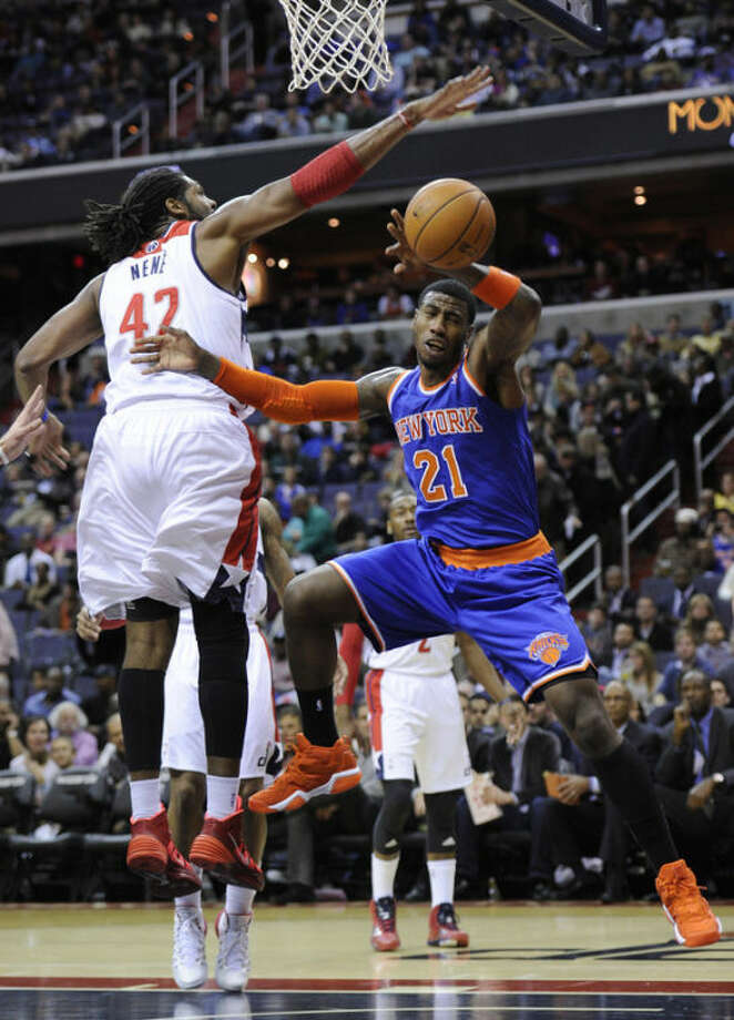 New York Knicks guard Iman Shumpert (21) loses the ball against Washington Wizards forward Nene (42), of Brazil, during the first half of an NBA basketball game on Saturday, Nov. 23, 2013, in Washington. (AP Photo/Nick Wass)