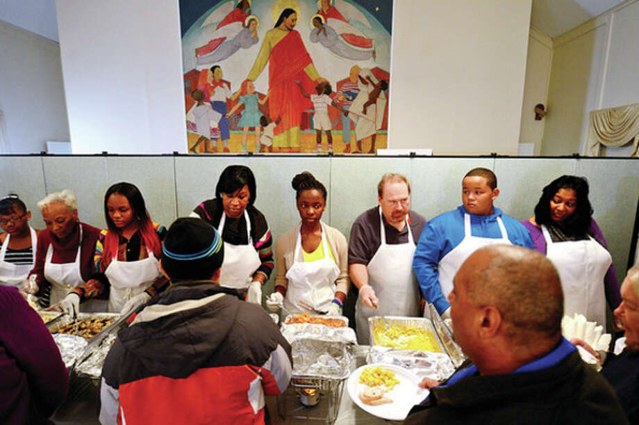 Hour photo / Erik Trautmann Volunteers serve up hot turkey and fixings during the Rev. Nellie Mann's annual pre-Thanksgiving feast for the needy at Calvary Baptist Church Saturday. / (C)2013, The Hour Newspapers, all rights reserved