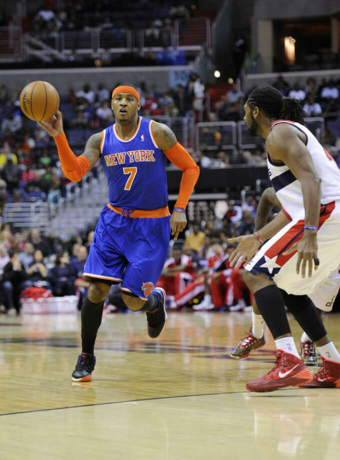 New York Knicks forward Carmelo Anthony (7) brings the ball upcourt against Washington Wizards forward Nene, right, of Brazil, during the first half of an NBA basketball game on Saturday, Nov. 23, 2013, in Washington. (AP Photo/Nick Wass)