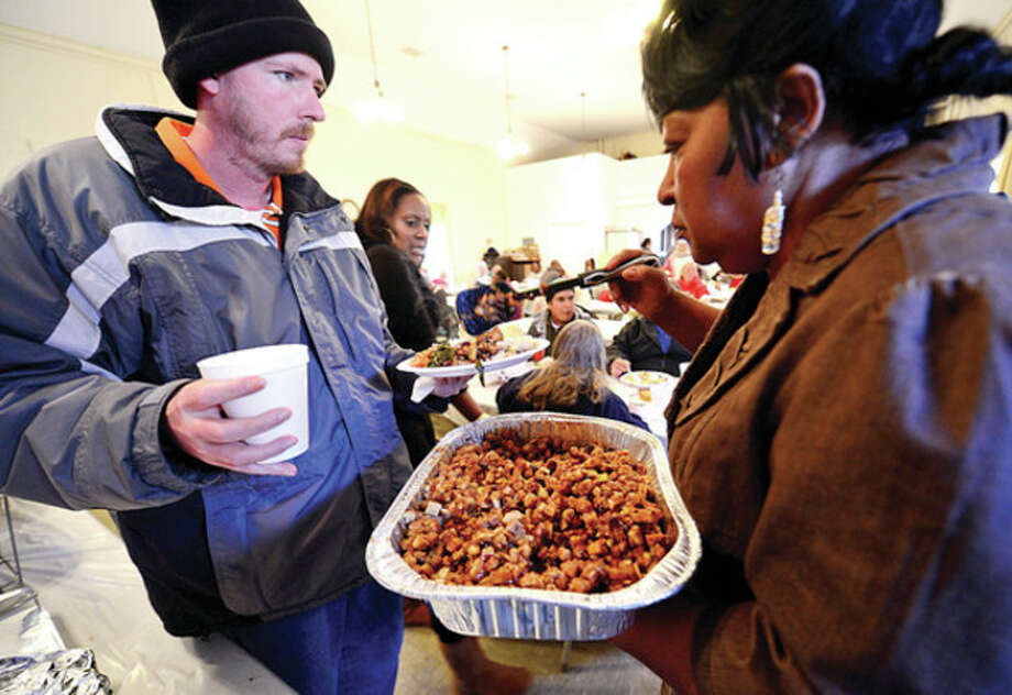 Hour photo / Erik TrautmannDaniel Wayne Eaves is served turkey stuffing by the Rev. Nellie Mann as she hosts her annual pre-Thanksgiving feast for the needy at Calvary Baptist Church on Saturday. / (C)2013, The Hour Newspapers, all rights reserved