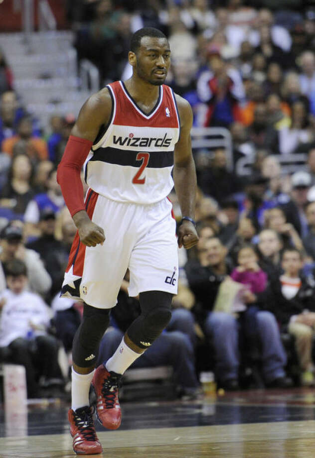 Washington Wizards guard John Wall (2) reacts during the first half of an NBA basketball game against the New York Knicks, Saturday, Nov. 23, 2013, in Washington. (AP Photo/Nick Wass)
