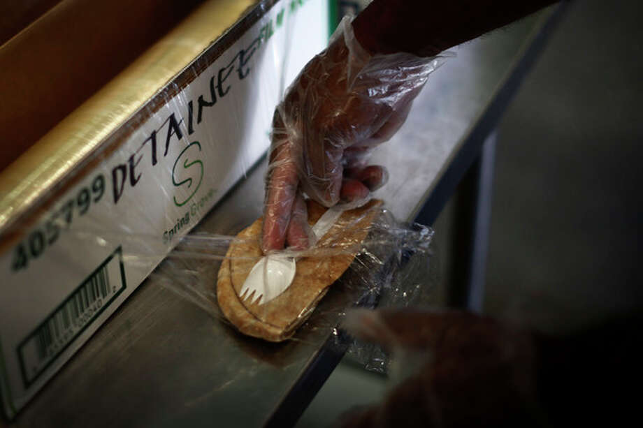 In this photo reviewed by the U.S. military, pita bread is wrapped with a plastic utensil during preparation of individual meals for detainees at Guantanamo Bay Naval Base, Cuba, Wednesday, Nov. 20, 2013. Today, 164 detainees are held at Guantanamo, costing U.S. taxpayers about $454 million each year -- about $2.7 million per detainee. (AP Photo/Charles Dharapak) / AP