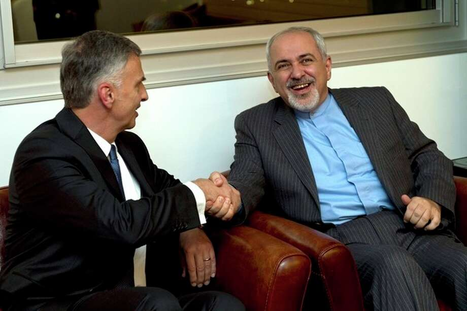 Switzerland's Foreign Minister Didier Burkhalter, left, shakes hands with Iranian Foreign Minister Mohammad-Javad Zarif, during a meeting at the Intercontinental Hotel prior to talks about Iran's nuclear programme in Geneva, Switzerland, Saturday, Nov. 23, 2013. (AP Photo / Keystone, Martial Trezzini) / POOL KEYSTONE