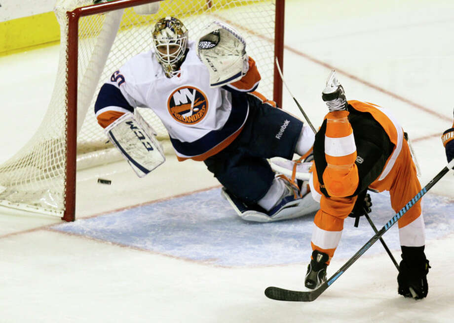 Philadelphia Flyers' Claude Giroux (not pictured) takes a shot for a goal past New York Islanders' goalie Kevin Poulin as the Flyers' Scott Hatnell (19) tumbles in the second period of an NHL hockey game, Saturday, Nov. 23, 2013, in Philadelphia. (AP Photo/Laurence Kesterson) / FR170723 AP
