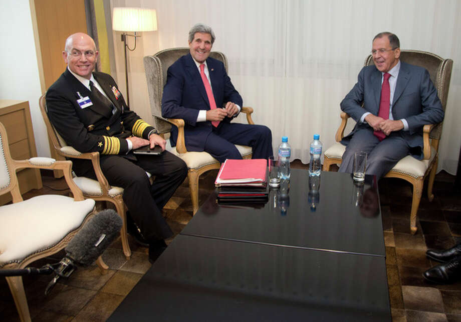 From left, Vice Admiral Kurt Tidd, U.S. Secretary of State John Kerry and Russia's Foreign Minister Sergei Lavrov look to a boom microphone held by a member of the media, lower left corner, as they sit together during a photo opportunity during a meeting, Saturday, Nov. 23, 2013, in Geneva, Switzerland, during the Iran nuclear talks. U.S. Secretary of State John Kerry and foreign ministers of other major powers joined Iran nuclear talks on Saturday, throwing their weight behind a diplomatic push to complete a deal after envoys reported progress on key issues blocking an interim agreement to curb the Iranian program in return for limited sanctions relief. (AP Photo/Carolyn Kaster, Pool) / Pool AP