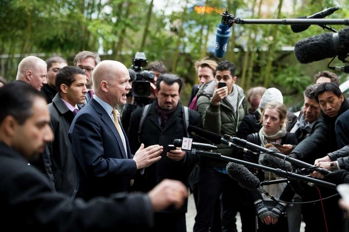 British Foreign Secretary William Hague speaks to journalists as he arrives at the Intercontinental Hotel prior to talks on Iran's nuclear program in Geneva, Switzerland, Saturday, Nov. 23, 2013. U.S. Secretary of State John Kerry and foreign ministers of other major powers joined Iran nuclear talks on Saturday, throwing their weight behind a diplomatic push to complete a deal after envoys reported progress on key issues blocking an interim agreement to curb the Iranian program in return for limited sanctions relief. (AP Photo/Keystone,Jean-Christophe Bott)
