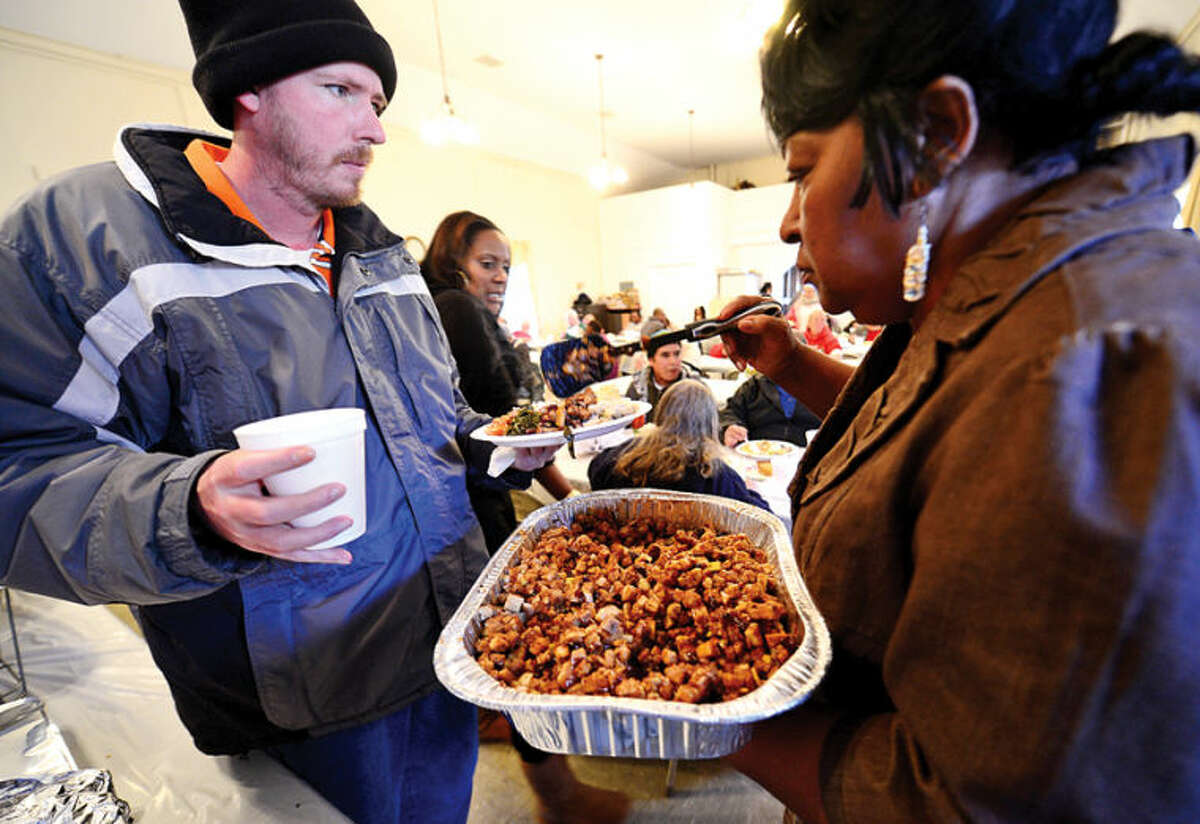 Hour photo / Erik Trautmann Daniel Wayne Eaves gets served up some stuffing by the Rev. Nellie Mann as Mann hosts her annual pre-Thanksgiving feast for the needy at Calvary Baptist Chrch Saturday.
