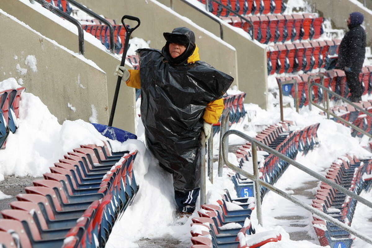 FILE - In this Dec. 20, 2009 file photo, workers clean snow from Giants Stadium prior to the start of an NFL game between the New York Jets and Atlanta Falcons, in East Rutherford, N.J. Instead of shrinking from the possibility that football?'s ultimate championship could be played in a blizzard, organizers of the first outdoor, cold-climate Super Bowl have decided to embrace the snow as the game?'s unofficial theme. In fact, some officials are positively hoping for snow. (AP Photo/Kathy Willens, File)