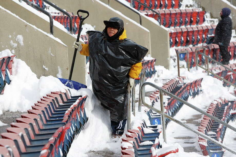 FILE - In this Dec. 20, 2009 file photo, workers clean snow from Giants Stadium prior to the start of an NFL game between the New York Jets and Atlanta Falcons, in East Rutherford, N.J. Instead of shrinking from the possibility that football's ultimate championship could be played in a blizzard, organizers of the first outdoor, cold-climate Super Bowl have decided to embrace the snow as the game's unofficial theme. In fact, some officials are positively hoping for snow. (AP Photo/Kathy Willens, File) / AP