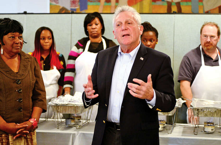 Hour photo / Erik Trautmann The new mayor of Norwalk, Harry Rilling, addresses volunteers and guests as the Rev. Nellie Mann hosts her annual pre-Thanksgiving feast for the needy at Calvary Baptist Church Saturday.