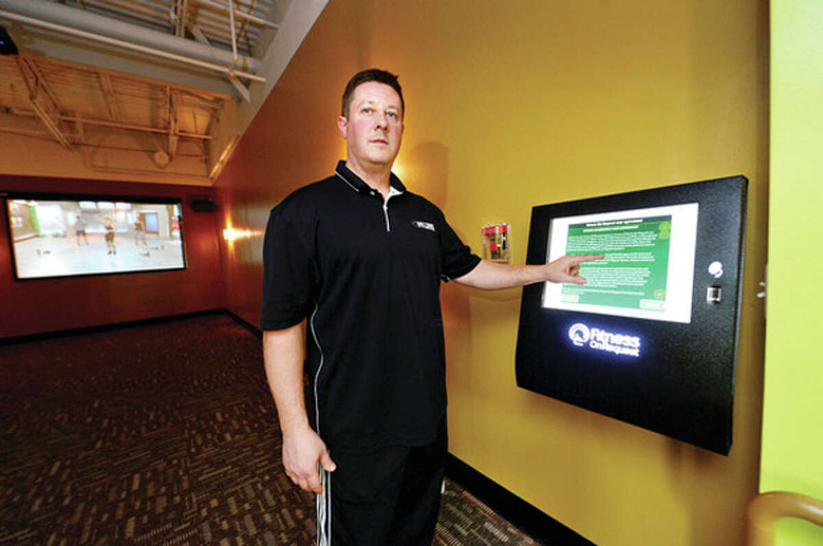 Hour photo / Erik Trautmann Jeff Kulhay, owner of Anytime Fitness, points out the new virtual trainer, Fitness on Request, in the new 24-hour gym on Westport Avenue in Norwalk.