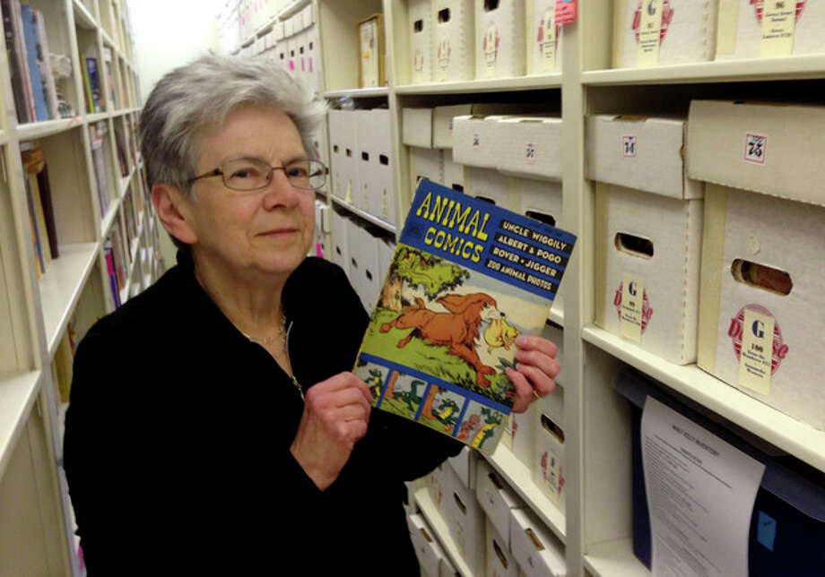 "In this Nov. 7, 2013 photo Maggie Thompson poses with ""Animal Comics"" in the addition she added to her Wisconsin home to house her tens of thousands of comic books. Thompson has put about 500 of her most treasured issues up for auction, including copies of ""Journey Into Mystery"" No. 83, the first appearance of Thor, and the first issue of ""The Avengers."" (AP Photo/Todd Richmond) / AP"