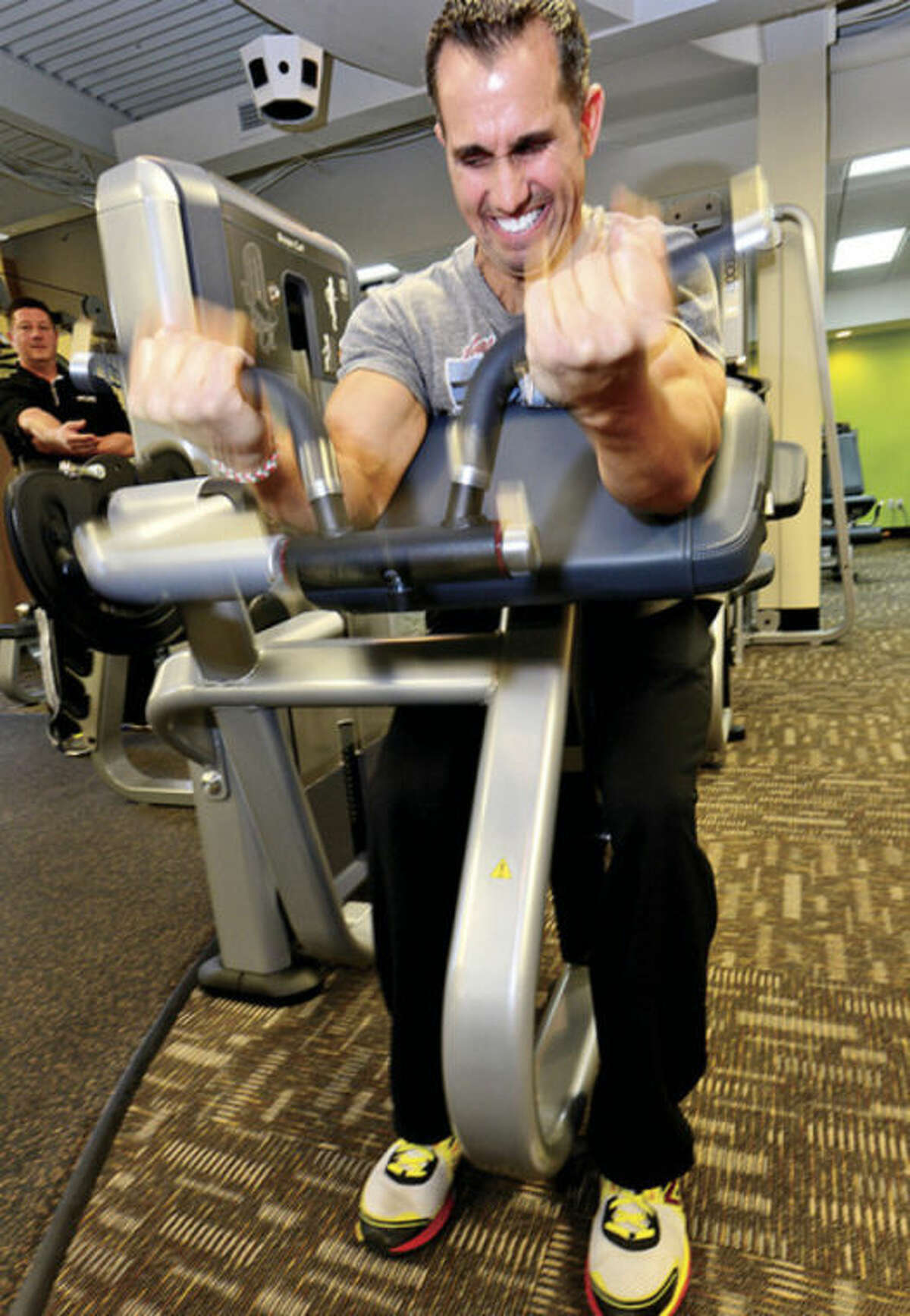 Hour photo / Erik Trautmann Joe Scaturchio, trainer at Anytime Fitness, demonstrates one of the machines in the new 24 hour gym.
