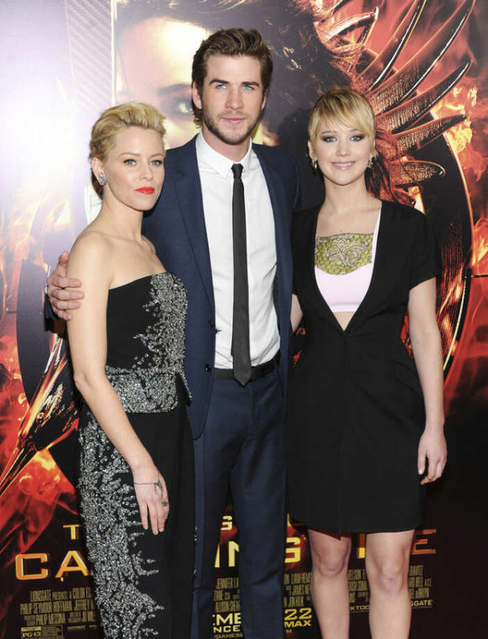 "From left, actors Elizabeth Banks, Liam Hemsworth and Jennifer Lawrence attend a special screening of ""The Hunger Games: Catching Fire"" at AMC Lincoln Square on Wednesday, Nov. 20, 2013, in New York. (Photo by Evan Agostini/Invision/AP)"