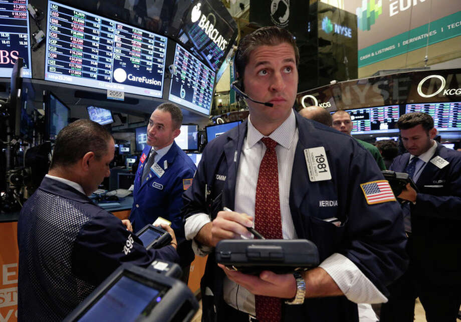 FILE - In this Tuesday, Nov. 19, 2013, file photo, Trader Thomas Donato, center, works on the floor of the New York Stock Exchange. Global stock markets, except Japan, were in the red Thursday Nov. 21, 2013 amid jitters over new signals from the U.S. Federal Reserve that it may cut monetary stimulus sooner than expected. (AP Photo/Richard Drew) / AP