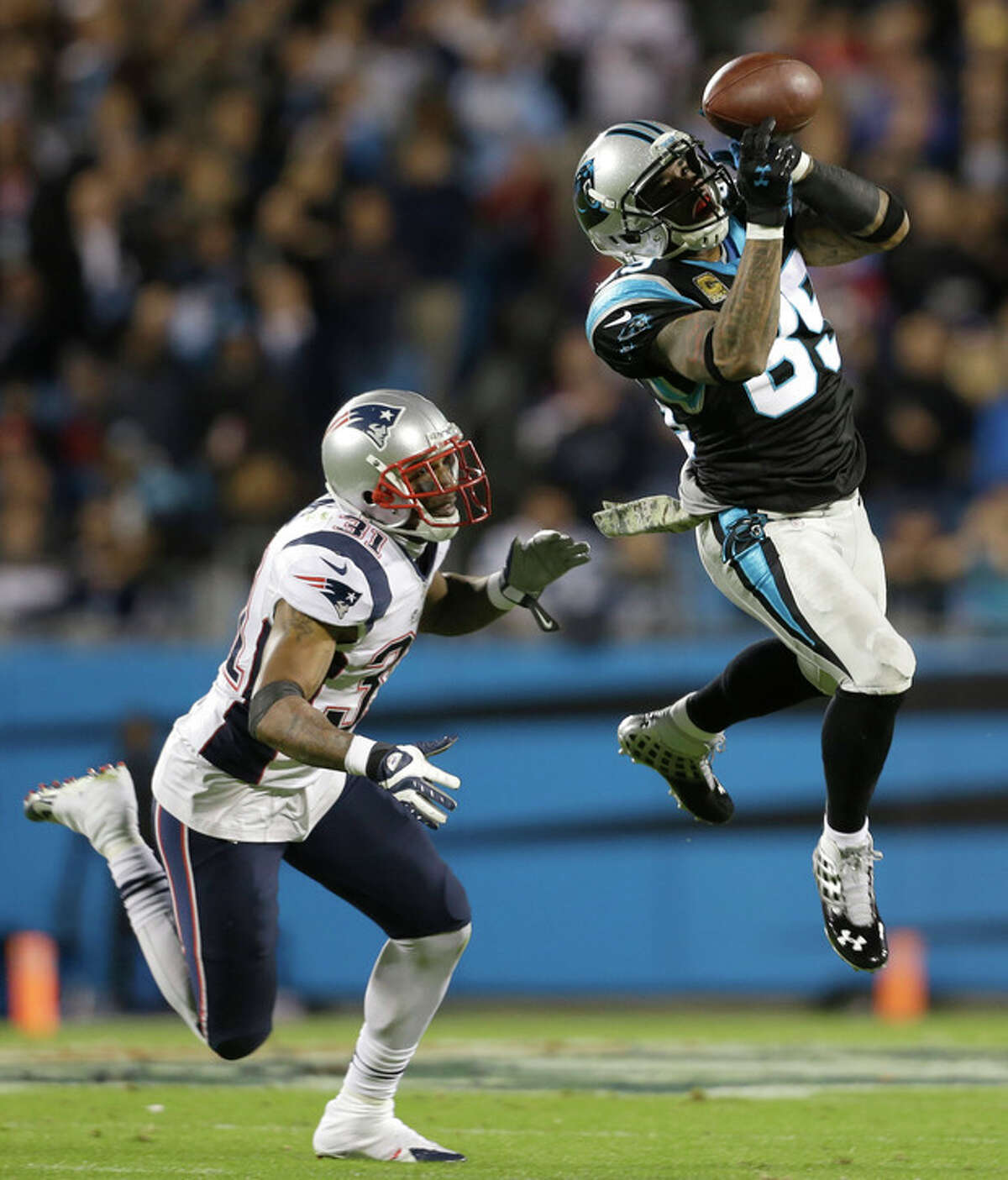 Carolina Panthers' Steve Smith (89) catches a pass as New England Patriots' Aqib Talib (31) defends during the first half of an NFL football game in Charlotte, N.C., Monday, Nov. 18, 2013. (AP Photo/Gerry Broome)