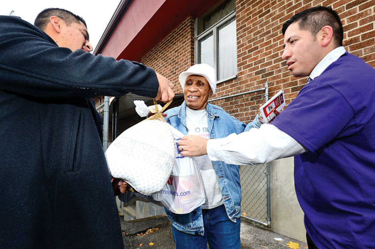 Hour photo / Erik Trautmann Grace Baptist Church, GE volunteers including Carlos Rivera and Diego Brito and the Bridgeport Rescue Mission assist nearly 400 Norwalk Housing Authority residents like Marie Cloiseau by providing warm coats and a turkey with other food stuffs Friday afternoon.