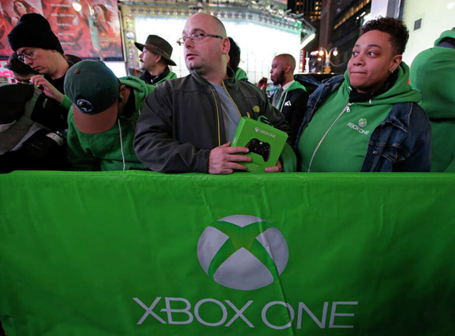 People line up outside the Best Buy Theater in Times Square awaiting the opportunity to purchase Microsoft's Xbox One video gaming console at a midnight sales launch, Thursday, Nov. 21, 2013, in New York. (AP Photo/Kathy Willens) / AP