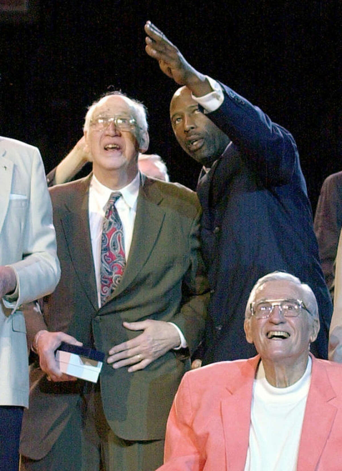 FILE - In this April 11, 2002, file photo, Minneapolis Lakers greats Vern Mikkelsen, left, and George Mikan, lower right, look up at banners honoring the team for winning five NBA titles in six years as former Los Angeles Lakers player James Worthy points during a halftime ceremony at an NBA basketball game in Los Angeles. Mikkelsen, a Hall of Fame basketball player who won four NBA titles with the Lakers, has died. He was 85. The Lakers say Mikkelsen died Thursday, Nov. 21, 2013. (AP Photo/Mark J. Terrill, File)