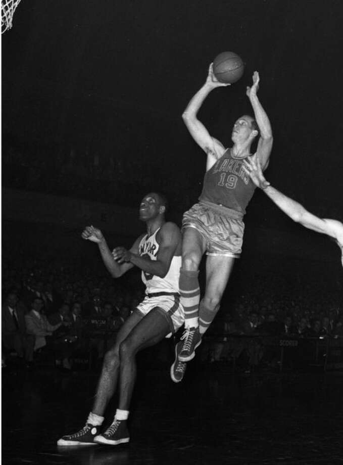 FILE - In this April 8, 1953, file photo, Minneapolis Lakers' forward Vern Mikkelsen (19) tries to score in the second period of an NBA basketball game against the New York Knickerbockers at 69th Regiment Armory in New York. Mikkelsen, a Hall of Fame basketball player who won four NBA titles with the Lakers, has died. He was 85. The Lakers say Mikkelsen died Thursday, Nov. 21, 2013. (AP Photo/Matty Zimmerman, File)