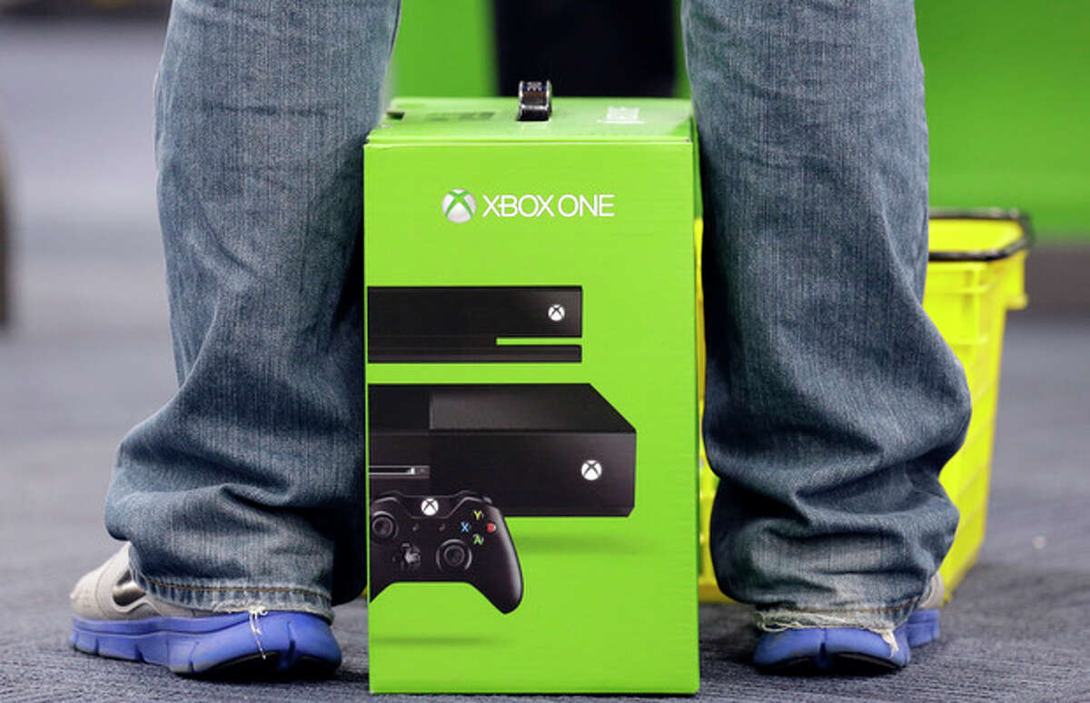 A man puts his newest XBox One on the floor after he purchased it at a Best Buy on Friday, Nov. 22, 2013., in Evanston, Ill. The Xbox One, which includes an updated Kinect motion sensor, cost $500. Microsoft is billing it as an all-in-one entertainment system rather than just a gaming console. (AP Photo/Nam Y. Huh)