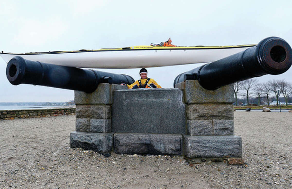 Hour photo / Erik Trautmann Michel Fitoussi hoists his kayak onto the cannon monument at Compo Beach in Westport for a photograph after paddling across the sound from his home in Long Island Friday.