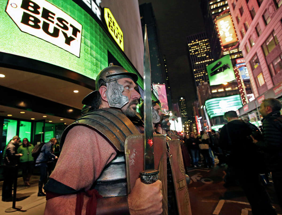 Xbox characters dressed as Roman soldiers stand at attention outside the Best Buy Theater in Times Square after arriving in advance of the midnight launch of Mikcrosoft's Xbox One video game console, Thursday, Nov. 21, 2013, in New York. (AP Photo/Kathy Willens)