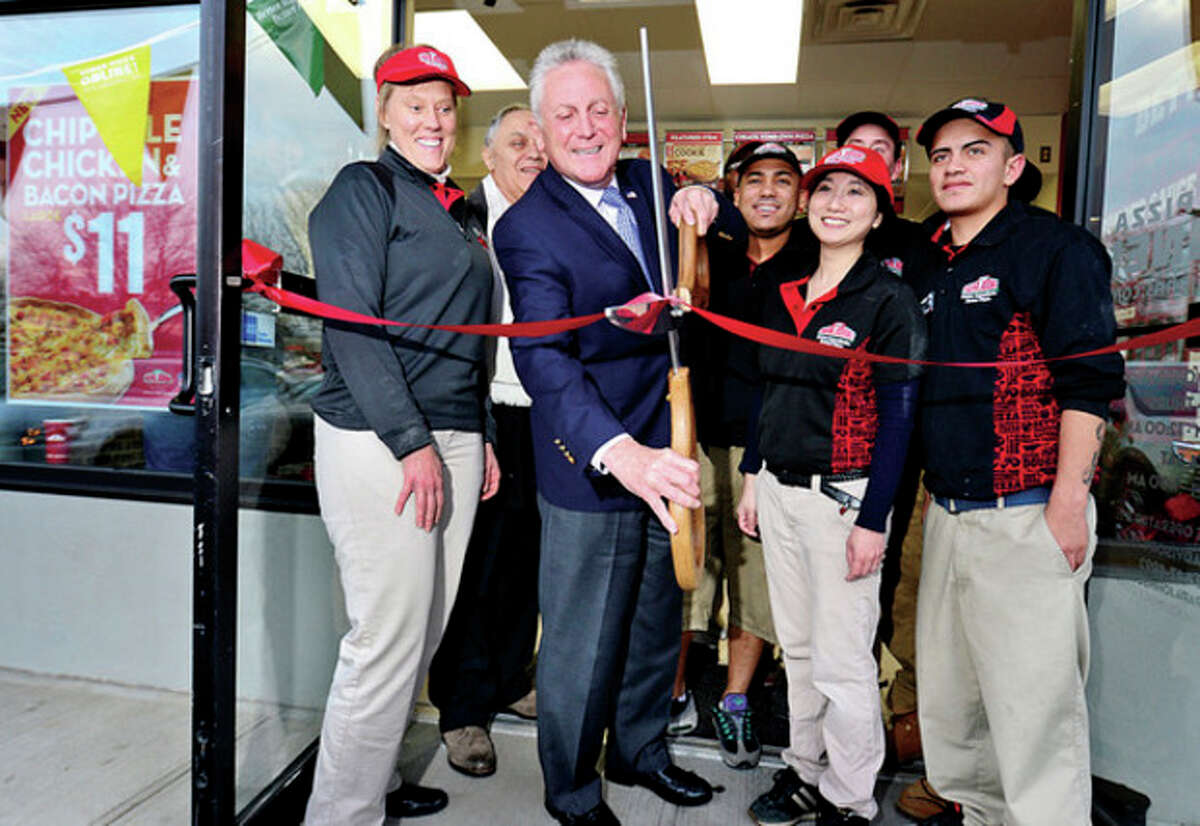 Hour photo / Erik Trautmann Norwalk mayor Harry Rilling cuts the ribbon at the grand opening for the new Papa John's on Main St while flanked by Papa John's franchise business director Jeannie Jefferson, property owner Joe Field, Papa John's employee Jonathan Rodriguez, franchise owner Jenny Wong and employee David Luna Friday.