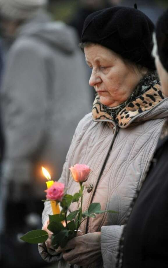 A woman holds a candles and flowers outside the collapsed Maxima supermarket in Riga, Latvia, Friday, Nov. 22, 2013. The reason for the collapse during shopping rush-hour Thursday was still not known but rescue and police officials said that possible theories include building's design flaws and poor construction work. (AP Photo/ Roman Koksarov)