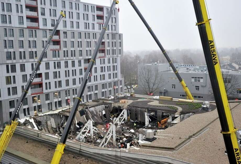 A view of collapsed Maxima supermarket in Riga, Latvia, Friday, Nov. 22, 2013. At least 32 people died, including three firefighters, after an enormous section of roof collapsed at a Latvian supermarket in the country's capital, emergency medical officials said Friday. The reason for the collapse during shopping rush-hour Thursday was still not known but rescue and police officials said that possible theories include building's design flaws and poor construction work. (AP Photo/ Roman Koksarov) / AP