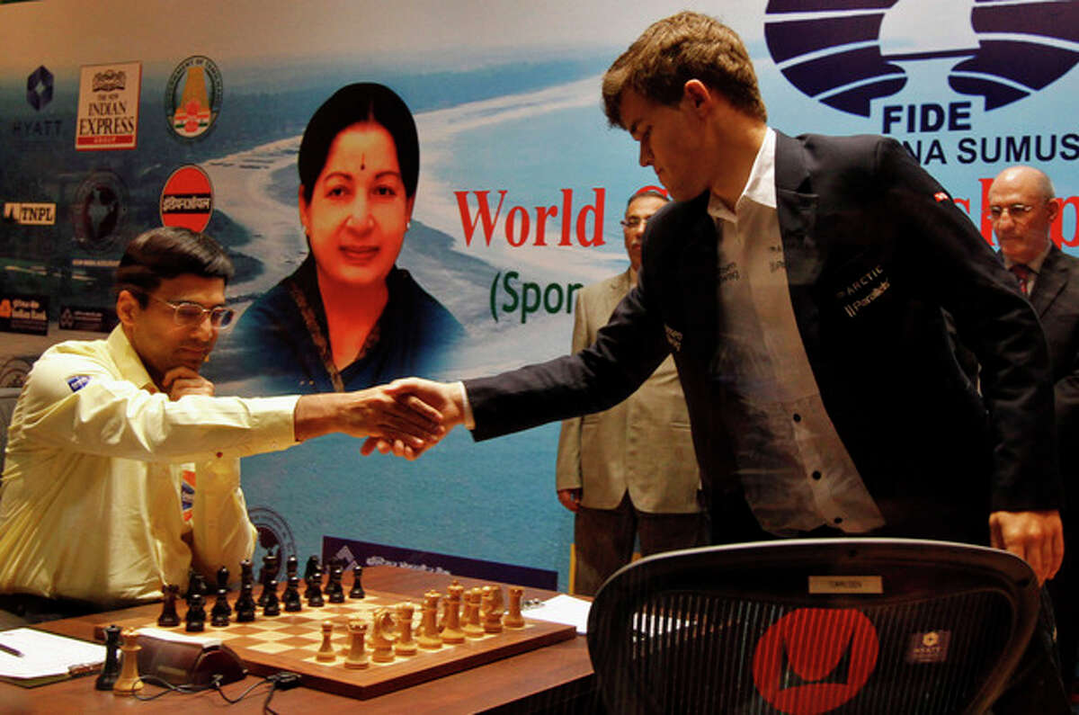 Norway?'s Magnus Carlsen, right, shakes hands with reigning world chess champion India?'s Viswanathan Anand during the Chess World Championship match in Chennai, India, Friday, Nov. 22, 2013. (AP Photo/Arun Sankar K.)