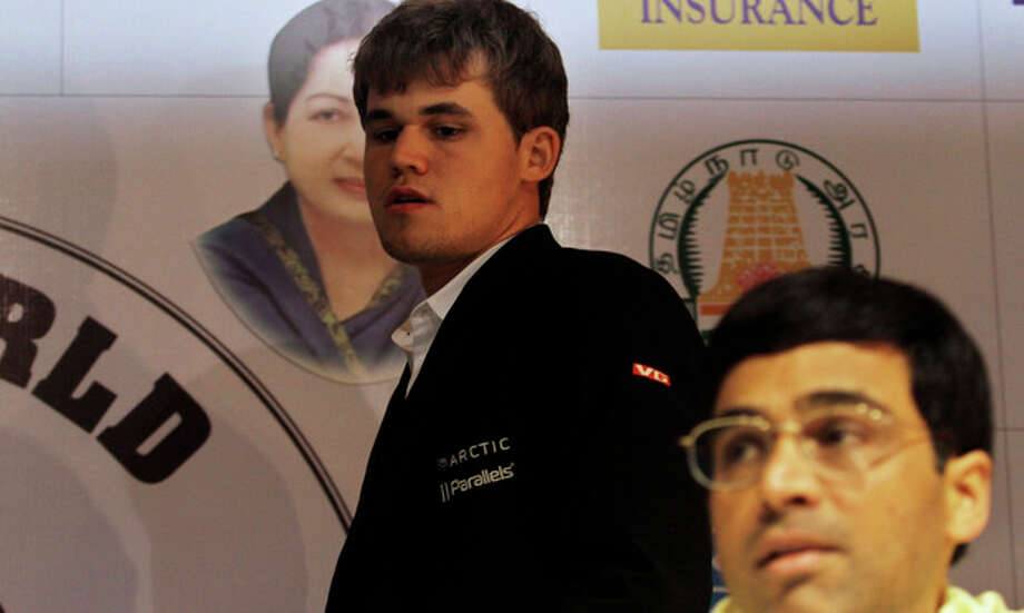 Norway's Magnus Carlsen, background, arrives to address a press conference after winning the match against India's Viswanathan Anand, foreground, during the Chess World Championship match in Chennai, India, Friday, Nov. 22, 2013. Anand's reign as the world champion came to an end Friday after Carlsen took the crown in the tenth game of the the World Chess championship. (AP Photo/Arun Sankar K.) / AP