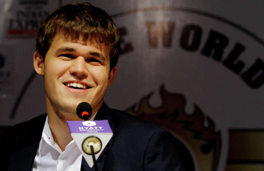 Norway's Magnus Carlsen smiles as he answers a question during a press conference after winning the match against India's Viswanathan Anand during the Chess World Championship match in Chennai, India, Friday, Nov. 22, 2013. Anand's reign as the world champion came to an end Friday after Carlsen took the crown in the tenth game of the the World Chess championship. (AP Photo/Arun Sankar K.) / AP
