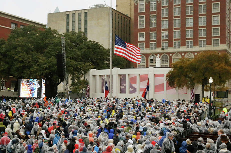 People gather before a ceremony to mark the 50th anniversary of the assassination of John F. Kennedy, Friday, Nov. 22, 2013, at Dealey Plaza in Dallas. President Kennedy's motorcade was passing through Dealey Plaza when shots rang out on Nov. 22, 1963.(AP Photo/Tony Gutierrez) / AP