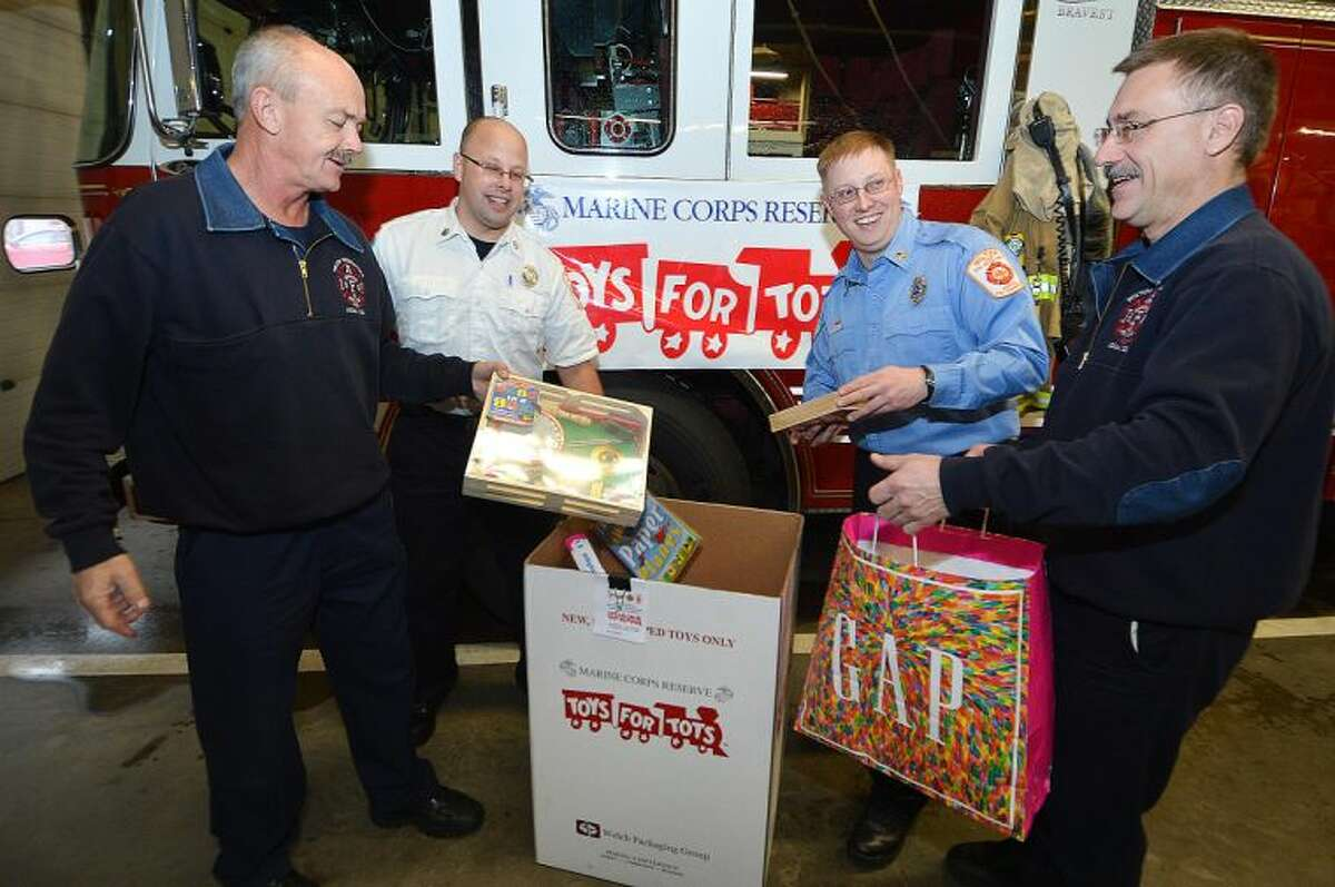 Hour Photo/Alex von Kleydorff. Ralph Nathanson, Kevin Czarnecki, Brian Elliott and Gary Fuoco are part of the Wilton Firefighters drive to collect toys for the Toys for Tots program.