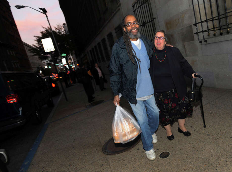 In this photo taken on Thursday, Nov. 14, 2013, freed prisoner Salim Sadiki, who served 37 years after being found guilty of rape, walks away from the courthouse in Baltimore with a friend after being released from prison. Faulty jury instructions given at trials held decades ago have led prosecutors in Maryland to release approximately 50 people, and some 200 prisoners could ultimately be released from Maryland prisons as a result. (AP Photo/Gail Burton) / FR4095 AP