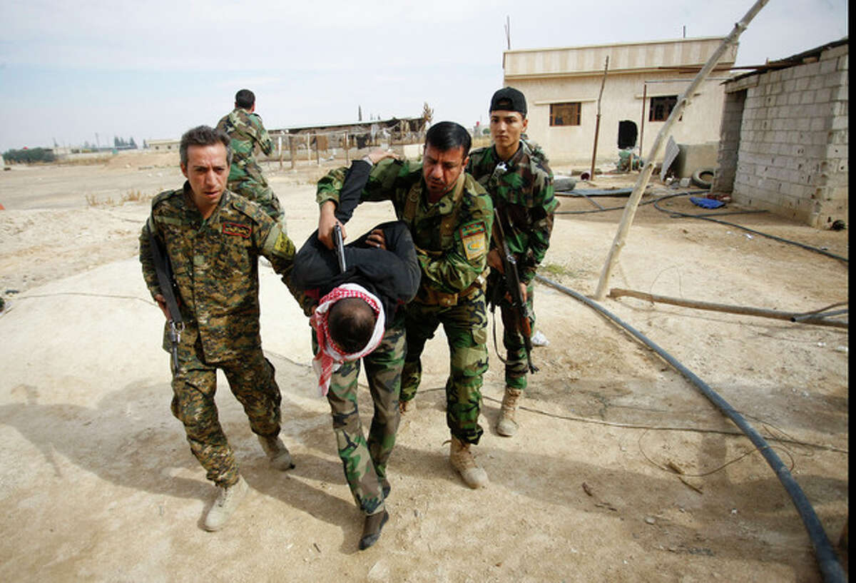 In this photo taken Friday, Nov. 22, 2013, Iraqi and Lebanese Shiite fighters from a group called the Hussein Brigade arrest a member of the Sunni-dominated Free Syrian Army in the town of Hatita, in the countryside of Damascus, Syria. (AP Photo/Jaber al-Helo)