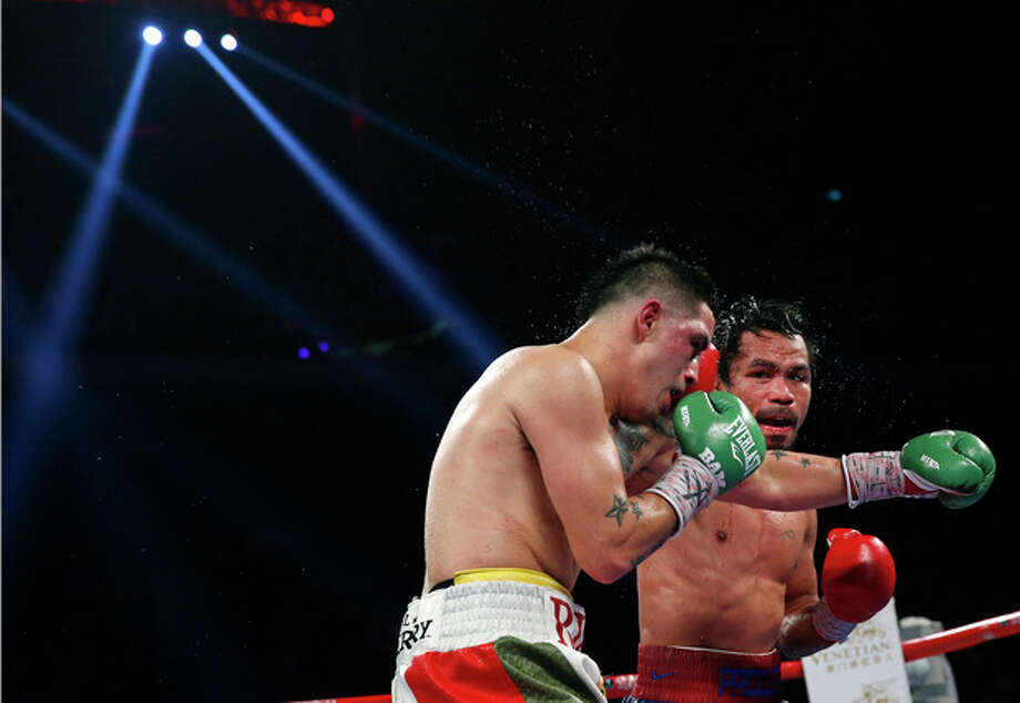 Manny Pacquiao from the Philippines, right, lands a right to Brandon Rios of the United States during their WBO international welterweight title fight Sunday, Nov. 24, 2013, in Macau. Pacquiao defeated Rios by unanimous decision on Sunday to take the WBO international welterweight title and return to his accustomed winning ways after successive defeats. (AP Photo/ Vincent Yu) / AP