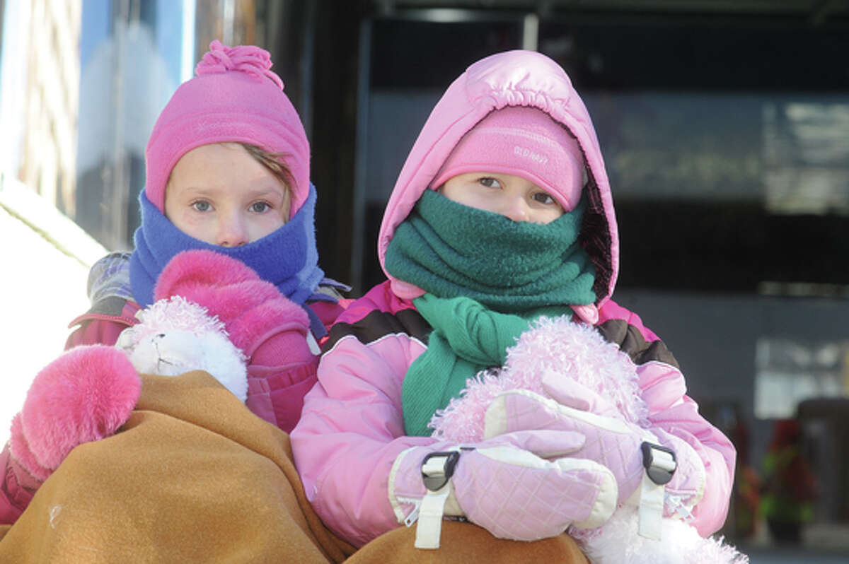 Emily Keenan, 7, and her sister Sarah, 5, bundled up Sunday in Stamford. The big balloons had to be grounded due to the high winds at the UBS Parade Spectacular. Hour photo/Matthew Vinci