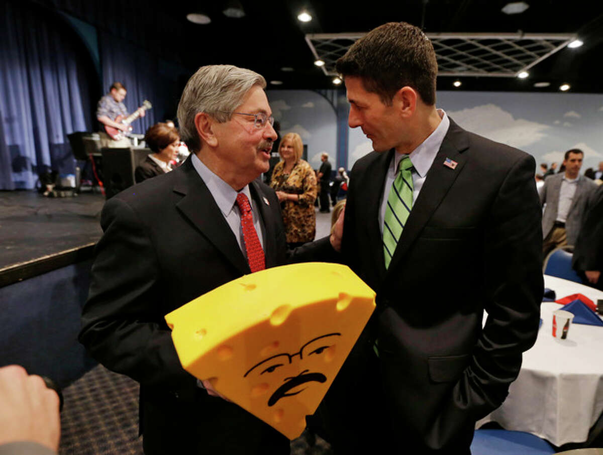 FILE - In this Nov. 16, 2013 photo, U.S. Rep. Paul Ryan, R-Wisc., talks with Iowa Gov. Terry Branstad, left, after presenting him with a cheesehead hat during Branstad's birthday bash and fundraiser in Altoona, Iowa. Branstad talked privately with Ryan before the fundraiser about a proposed reduction in the minimum amount of ethanol in the nation?'s fuel supply. (AP Photo/Charlie Neibergall, File)