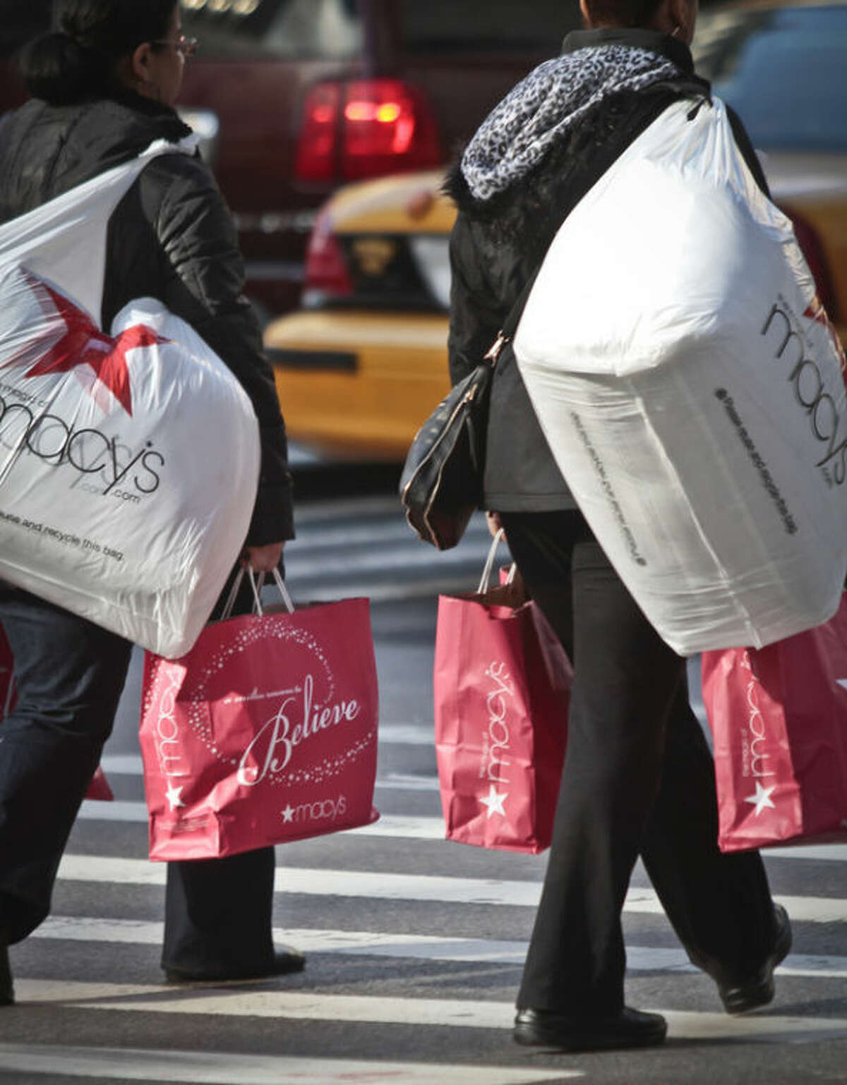 Shoppers carry Macy's bags while crossing an intersection outside Macy's on Saturday, Nov. 23, 2013, in New York. (AP Photo/Bebeto Matthews)
