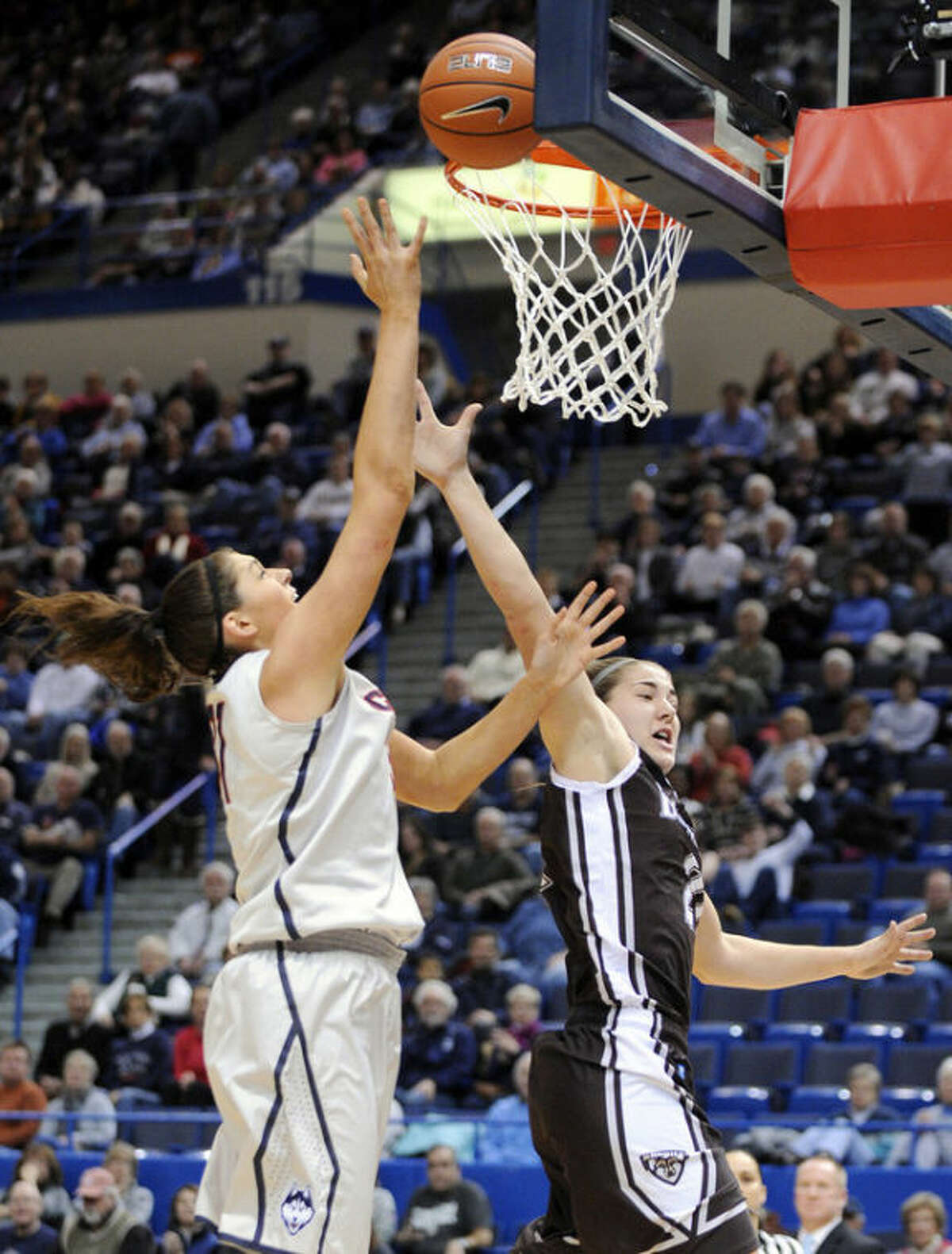 Connecticut's Stefanie Dolson, left, shoots over St. Bonaventure's Nyla Rueter during the first half of an NCAA college basketball game in Hartford, Conn., on Sunday, Nov. 24, 2013. (AP Photo/Fred Beckham)