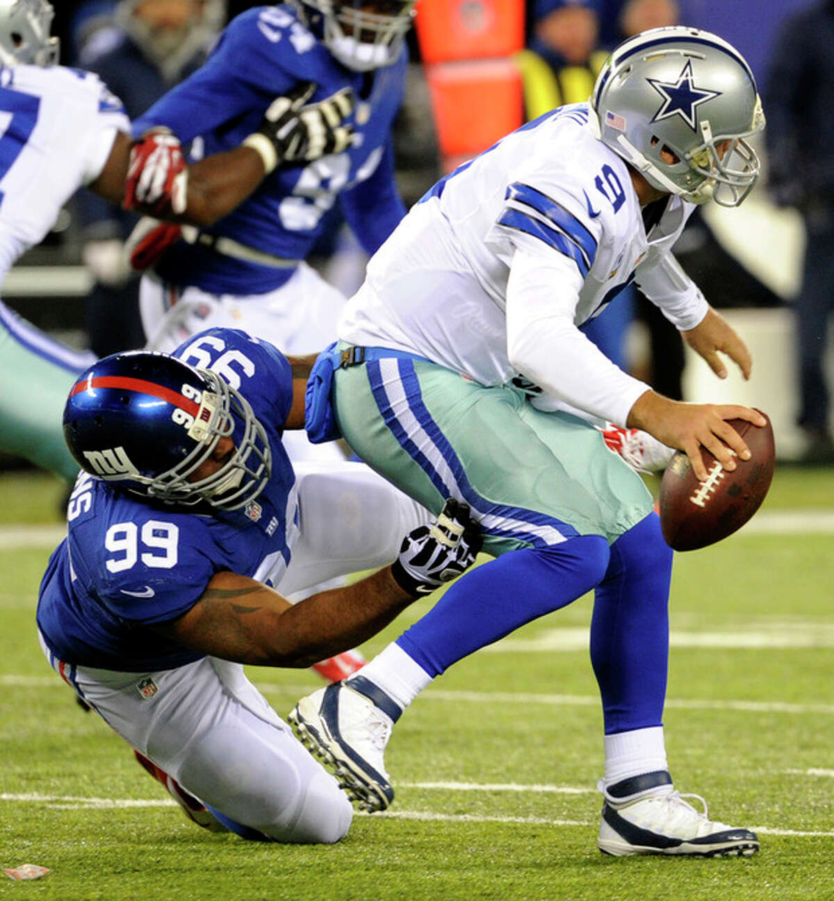 Dallas Cowboys quarterback Tony Romo (9) is sacked by New York Giants Cullen Jenkins (99) during the first half of an NFL football game, Sunday, Nov. 24, 2013, in East Rutherford, N.J. (AP Photo/Bill Kostroun)