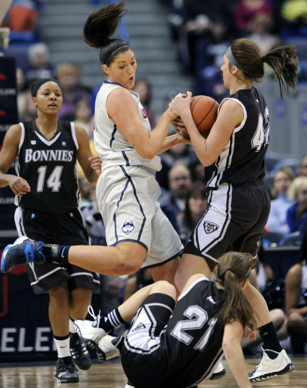 Connecticut's Stefanie Dolson, second from left, fights for a rebound with St. Bonaventure's Katie Healy, right, as St. Bonaventure's Nyla Rueter (21) and Gabby Richmond (14) stand by during the first half of an NCAA college basketball game in Hartford, Conn., on Sunday, Nov. 24, 2013. (AP Photo/Fred Beckham)