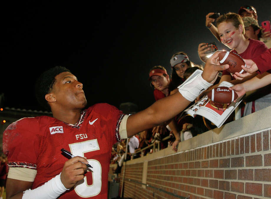FILE - In a Saturday, Nov. 23, 2013 file photo, Florida State quarterback Jameis Winston (5) signs autographs after an NCAA college football game against Idaho, in Tallahassee, Fla. Its handling of sexual assault allegations against Florida State quarterback Winston is just the latest controversy to hit the Tallahassee Police Department. A handful of grand juries recently have issued scathing reports about how some officers have conducted themselves in the line of duty.(AP Photo/Phil Sears, File) / FR170567 AP
