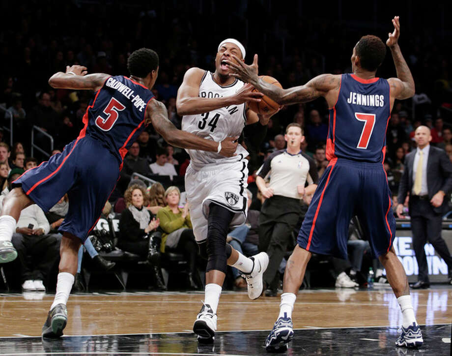 Detroit Pistons guard Kentavious Caldwell-Pope (5) fouls Brooklyn Nets forward Paul Pierce (34) as Detroit Pistons guard Brandon Jennings (7) defends in the first half of an NBA basketball game, Sunday, Nov. 24, 2013, in New York. (AP Photo/Kathy Willens) / AP