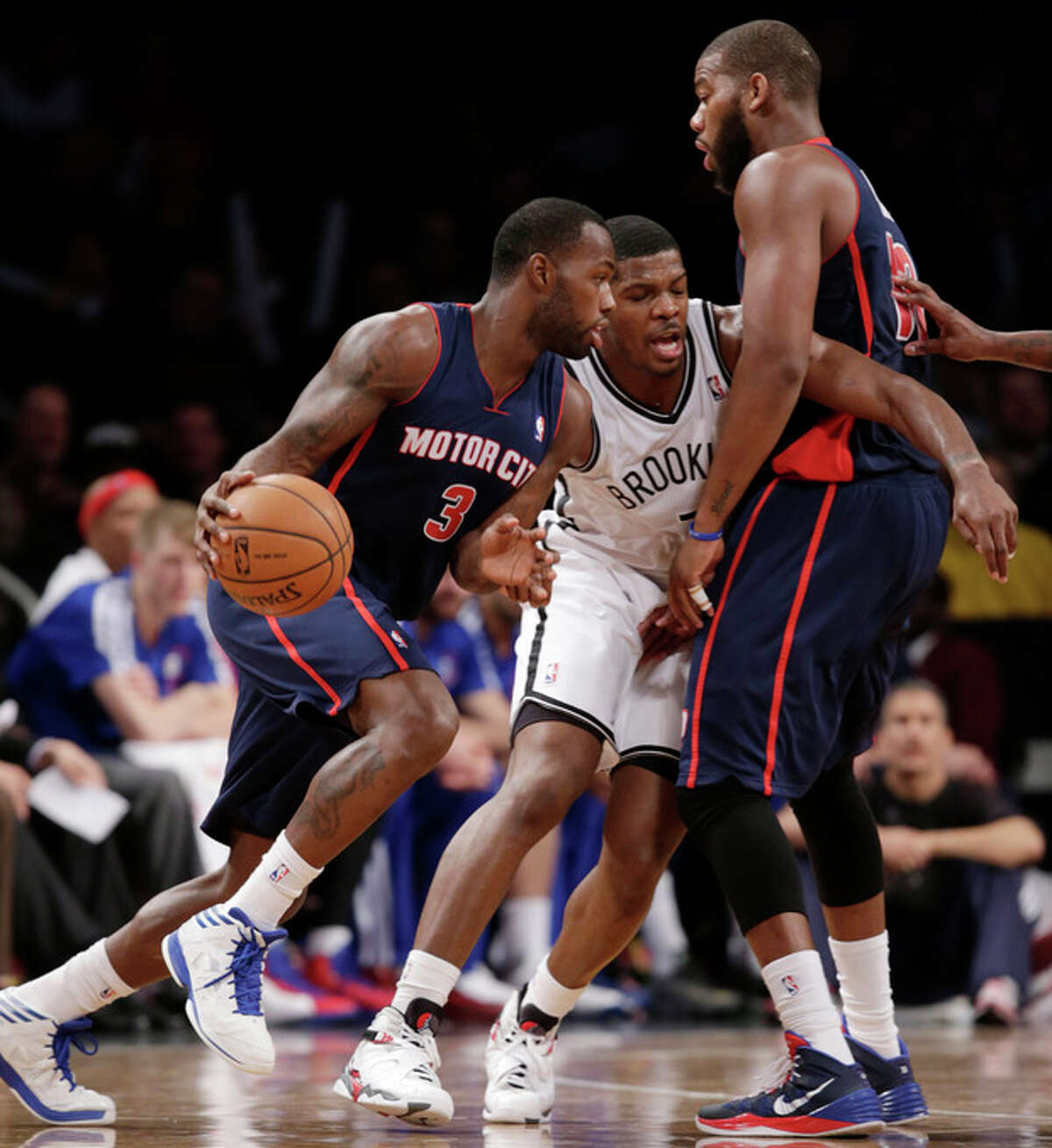 Brooklyn Nets guard Joe Johnson (7) defends as Detroit Pistons guard Rodney Stuckey (3) drives to the basket with Pistons forward Greg Monroe (10) looking on in the first half of an NBA basketball game, Sunday, Nov. 24, 2013, in New York. (AP Photo/Kathy Willens)