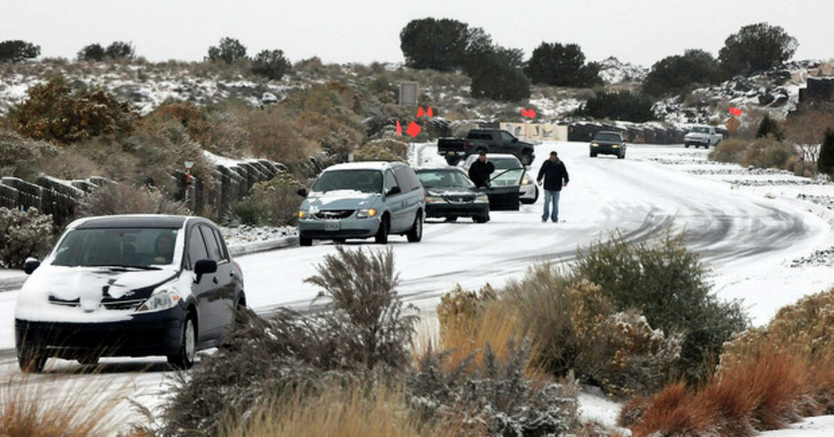 Cars slide on Paseo del Norte Sunday, Nov.24, 2013, in Albuquerque, N.M., after a winter storm hit New Mexico over the weekend making driving difficult for drivers. A large storm already blamed for at least eight deaths in the West slogged through Oklahoma, Texas, New Mexico and other parts of the southwest Sunday as it slowly churned east ahead of Thanksgiving.(AP PhotosAlbuquerque Journal, Jim Thompson) THE SANTA FE NEW MEXICAN OUT